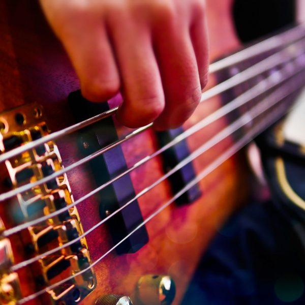 Closeup of hand playing bass guitar during a performance.